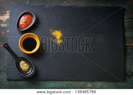 Three types of sauce - tomato sauce soy sauce and pesto sauce on a stone and wooden background top view with copy space