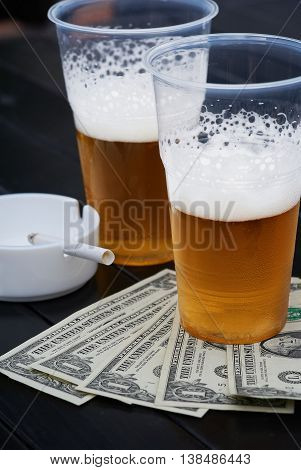 Two glasses of beer fan-shaped dollars and ash tray with
