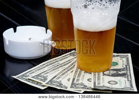 Two glasses of beer fan-shaped dollars and ash tray with cigarette
