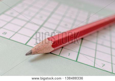 Red Pencil And Sudoku Crossword. Popular Logic Game. Macro Shot.