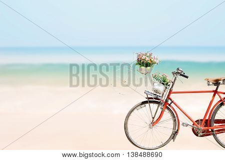 Old red Bicycle with basket flowers on blured beach tropical sea background