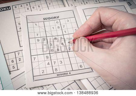 Hand Holding Pencil Is Solving Sudoku Crossword.