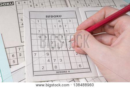 Hand Is Solving Sudoku Crossword, Popular Puzzle Game.