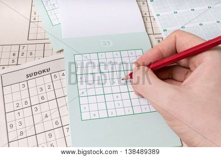 Hand Is Holding Pencil And Is Solving Sudoku Crossword With Numb