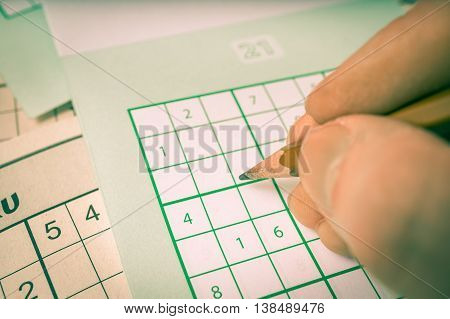 Hand Is Writing Numbers In Grid Of Popular Logic Game Sudoku.