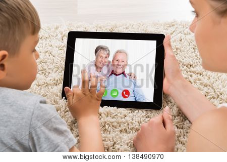 Close-up Of Mother And Son Videoconferencing On Digital Tablet At Home