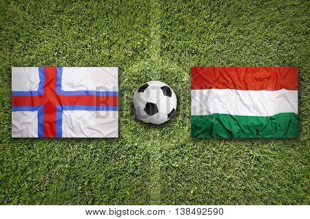 Faeroe Islands Vs. Hungary Flags On Soccer Field