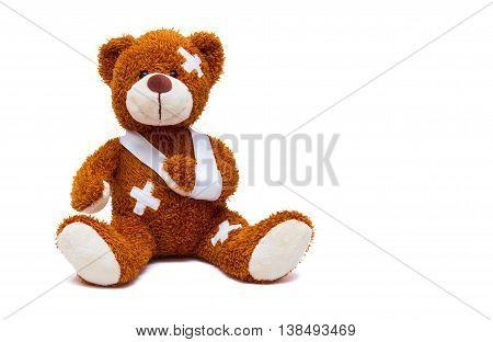 Injured teddy bear with bandages on white background