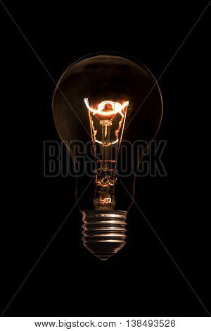 Glowing light bulb without wires on black background.