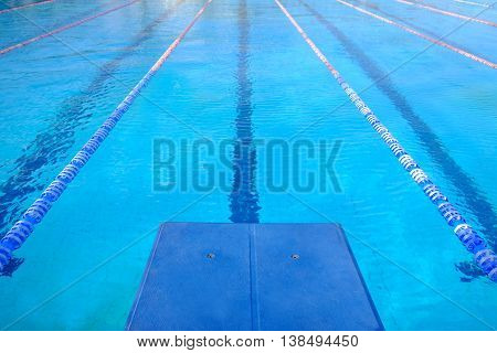 View on the swimming-pool with blue water a platform and a lane of the swimming-pool.