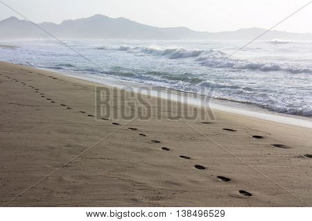 Footprints in the sand along the famous beach Costa Rei in Sardinia with mountains on the background