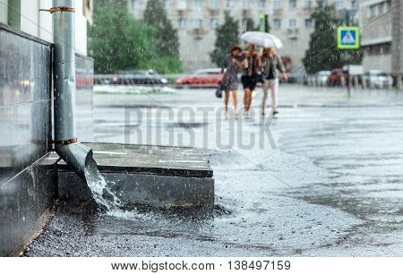Rain water flowing from metal downspout during a flood. Three women cross the road at backgrond bokeh. Concept of protection against heavy downpour , rainy weather
