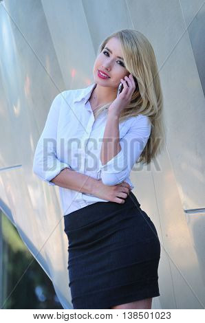 Professional young woman making a business call on mobile phone in the city