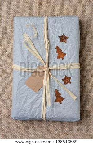 Top view of a tissue paper wrapped Christmas present on a burlap surface. Tied with Raffia with tin stars and trees
