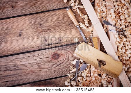 Wooden planer, table from old wood, natural building materials, woodwork and antique hand tools, carrying out carpentry, tool kit for joinery, wood sawdust, old wood texture poster