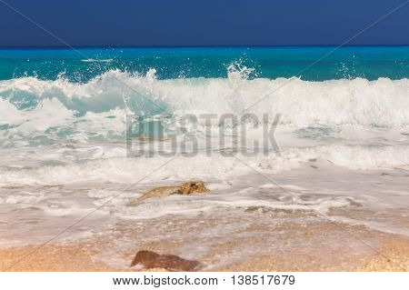 Tropical seascape. View of waves splashing on shore at beach against sky during daytime