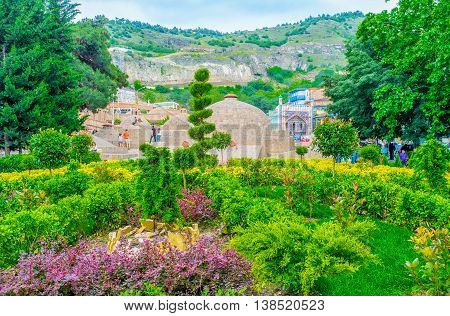 TBILISI GEORGIA - MAY 28 2016: The beautiful green garden with trimmed trees and large domes of the sulfur baths in Abanotubani on May 28 in Tbilisi.