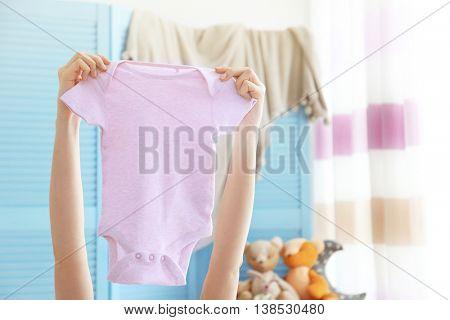 Female hand holding baby bodysuit in interior of child's room
