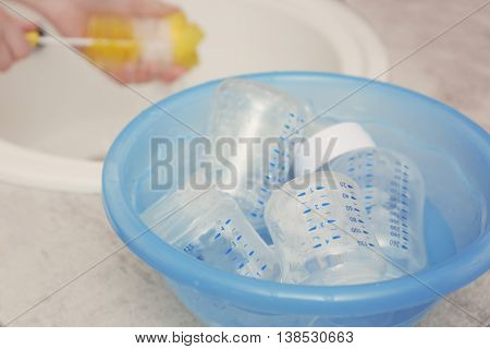 Woman hands washing baby bottles in plastic blue basin