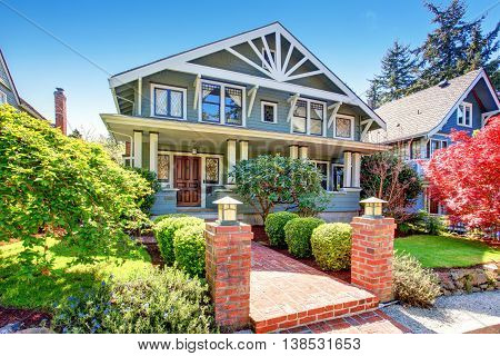 Large luxury blue craftsman classic American house exterior. View of brick walkway decorated with trimmed hedges. poster