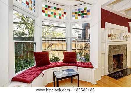 Cozy Sitting Area With Wide Decorative Windows And Red Pillows.