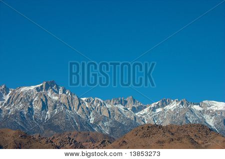Jagged snow capped peaks behind brown hills
