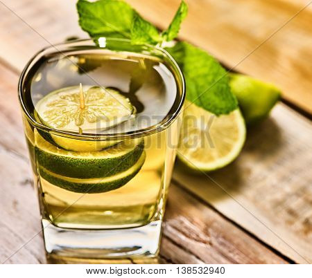 Alcohol cocktail. On wooden boards is glass with alcohol green transparent drink. A drink number hundred sixty four mohito cocktail with lime. Close up of country life.