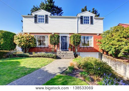 Beautiful Curb Appeal Of Two Level House With Brick And White Siding.