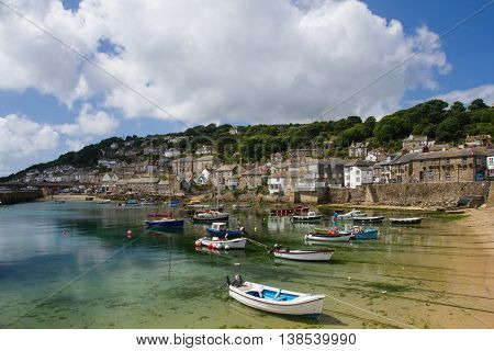 MOUSEHOLE, CORNWALL, UK - JUNE 26, 2016. The picturesque Cornish fishing village of Mousehole in Cornwall with its small harbour and surrounding fishermen's cottages is a popular tourist destination in England.