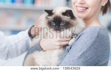 Smiling woman and her cat at the veterinary clinic a doctor is examining the pet