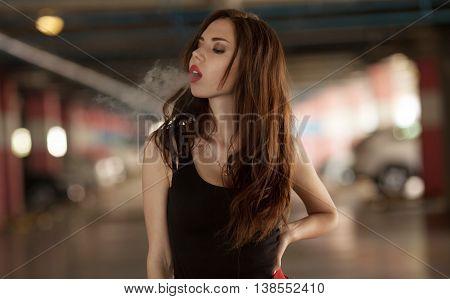 Young beautiful woman smoking ( vaping ) e-cigarette with smoke in car luke