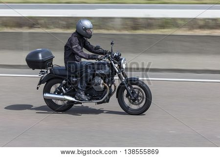 FRANKFURT GERMANY - JULY 12 2016: Motorcyclist on the Moto Guzzi V7 motorcycle driving on the highway in Germany