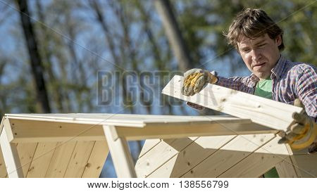 Carpenter or homeowner fitting a section of wood to an outdoor timber frame hut against a background of woodland trees in a DIY concept.