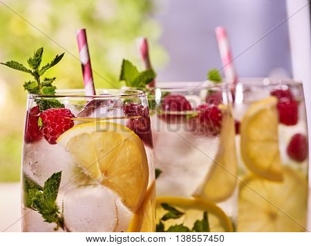 Top of three glasses with alcohol cocktail and ice cubes. Drink number hundred seventy six cocktail raspberry mohito with straw and lime and mint leaf. Outdoor. Light background.