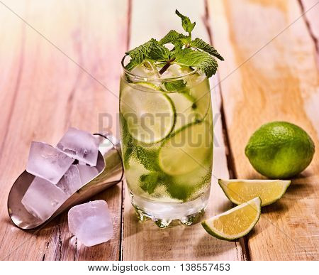 Alcohol drink. On wooden boards is glass with alcohol drink and ice cubes. A drink number hundred sixty seven cocktail mohito and scoop ice . Country life still life . Light background.