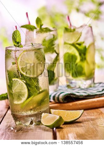 Alcohol cocktail. On wooden boards group of glasses with alcohol drink and ice cubes. A drink number hundred seventy two cocktail mohito with mint leaf. Country life on wooden table. Light background.