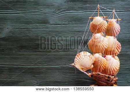 Beautiful sea composition with ship seashells copy space on wooden background. Marine still life with toy model of ship made of cockleshells. Travel and adventure concept