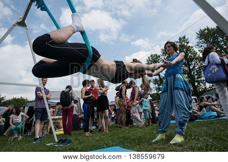 Saint-Petersburg Russia - June 26 2016: Performing yoga asanas in hammocks. The instructor teaches the newcomers during the celebration of World Day of Yoga.