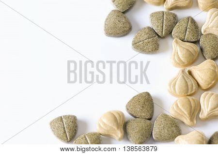 Close-up of herbal supplement pills on white background