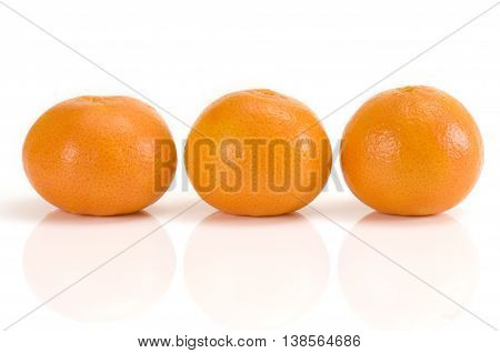 Three fresh mandarins isolated on white background