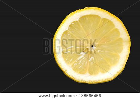 Fresh slice of lemon on black background