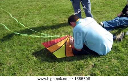 A Man Sitting On The Grass Fixing A Kit