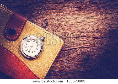 Pocketbook and old pocket watch on wooden background.