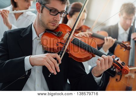Classical music symphony orchestra string section performing male violinist playing on foreground music and teamwork concept poster