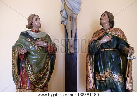 STITAR, CROATIA - AUGUST 27: St Valentine martyr and St. Vitus martyr under the crucifix in the chapel in the village Stitar, Croatia on August 27, 2015