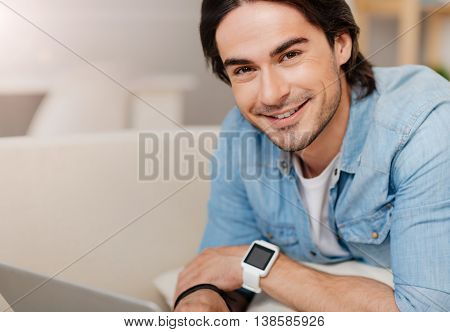 Digital generation. Positive delighted handsome man using laptop and resting on the couch while smiling
