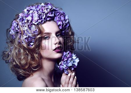 Portrait of beautiful woman with flower crown from blue hydrangea.