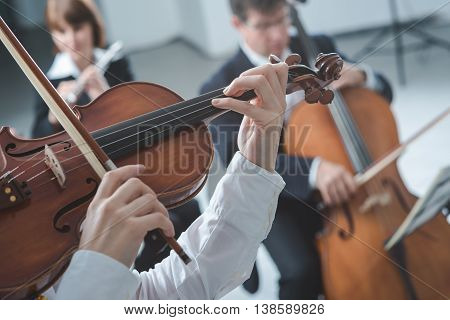 Classical music symphony orchestra string section performing female violinist playing on foreground hands close up poster