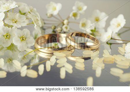 Close-up of wedding rings on background of rice and flowers