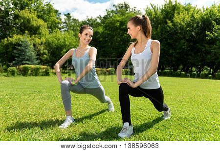 Keep the tempo. Cheerful happy young women stretching and doing sport exercises outdoors